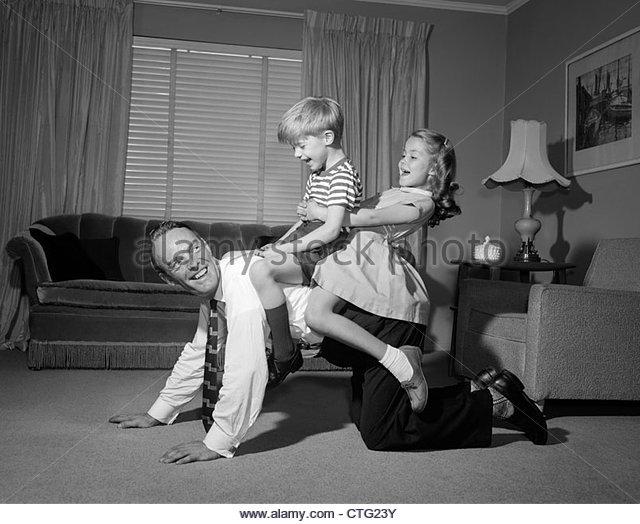 1950s-1960s-dad-carrying-boy-girl-piggyback-on-living-room-floor-ctg23y.jpg